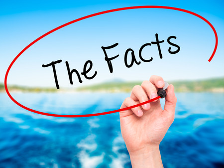 Man Hand writing The Facts  with black marker on visual screen. Isolated on nature. Business, technology, internet concept. Stock Photo