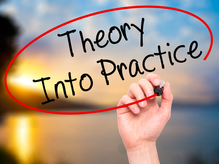 Man Hand writing Theory Into Practice with black marker on visual screen. Isolated on nature. Business, technology, internet concept. Stock Photo