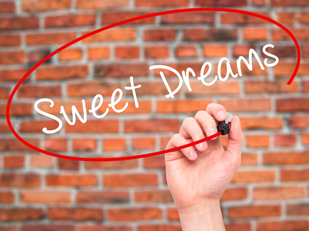 endearment: Man Hand writing Sweet Dreams with black marker on visual screen. Isolated on bricks. Business, technology, internet concept.