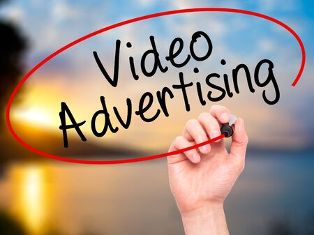 infomercial: Man Hand writing Video Advertising with black marker on visual screen. Isolated on nature. Business, technology, internet concept. Stock Photo