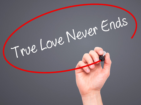 need direction: Man Hand writing True Love Never Ends with black marker on visual screen. Isolated on grey. Business, technology, internet concept. Stock Photo