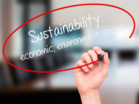 economic theory: Man Hand writing Sustainability  economic, environment, social with black marker on visual screen. Isolated on office. Business, technology, internet concept.