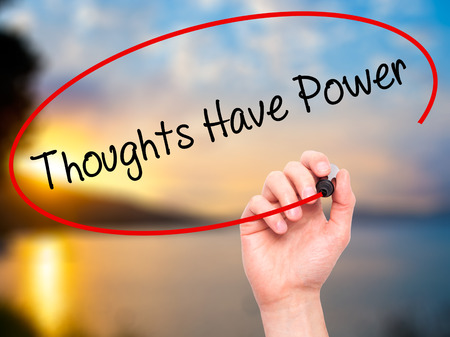 Man Hand writing Thoughts Have Power with black marker on visual screen. Isolated on nature. Business, technology, internet concept. Stock Photo