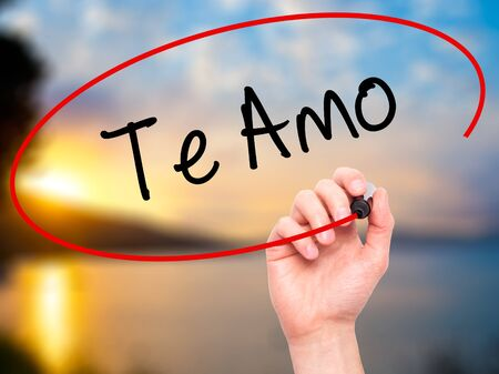 Man Hand writing Te Amo ( I Love You In Spanish) with black marker on visual screen. Isolated on nature. Business, technology, internet concept. Stock Photo Stock Photo