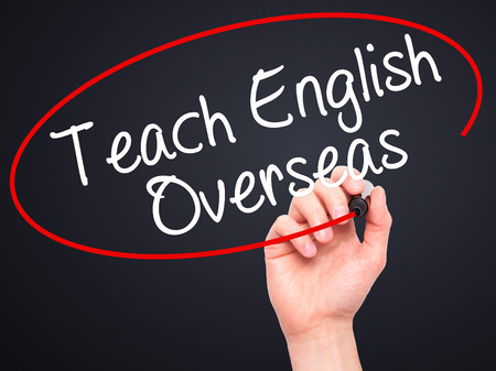 Man Hand writing Teach English Overseas with black marker on visual screen. Isolated on black. Business, technology, internet concept. Stock Photo Stock Photo