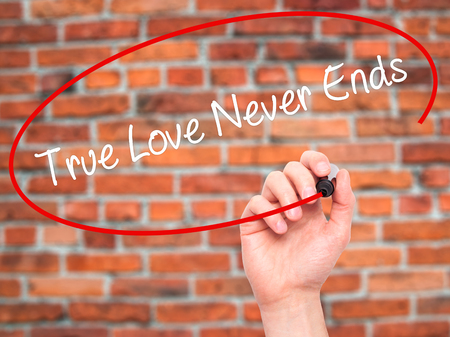 need direction: Man Hand writing True Love Never Ends with black marker on visual screen. Isolated on bricks. Business, technology, internet concept. Stock Photo