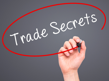 trade secret: Man Hand writing Trade Secrets with black marker on visual screen. Isolated on grey. Business, technology, internet concept. Stock Photo