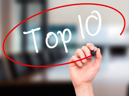 Man Hand writing Top 10 with black marker on visual screen. Isolated on office. Business, technology, internet concept. Stock Photo Archivio Fotografico