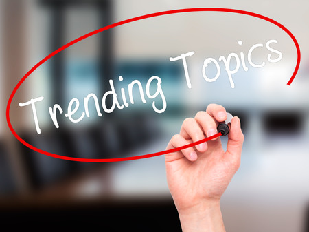 business trending: Man Hand writing Trending Topics with black marker on visual screen. Isolated on background. Business, technology, internet concept. Stock Photo