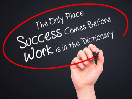Man Hand writing The Only Place Success Comes Before Work is in the Dictionary with black marker on visual screen. Isolated on black. Business, technology, internet concept. Stock Photo
