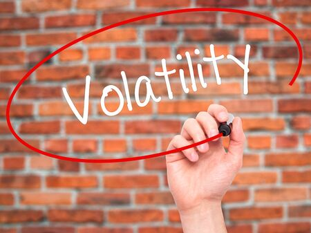volatility: Man Hand writing Volatility with black marker on visual screen. Isolated on bricks. Business, technology, internet concept. Stock Photo Stock Photo