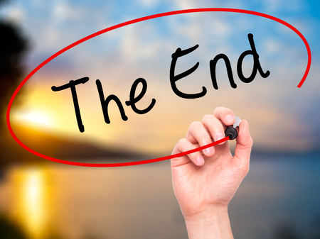imminent: Man Hand writing The End with black marker on visual screen. Isolated on nature. Business, technology, internet concept. Stock Photo