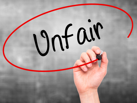 advantaged: Man Hand writing Unfair with black marker on visual screen. Isolated on background. Business, technology, internet concept. Stock Photo