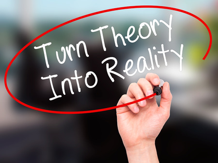 Man Hand writing Turn Theory Into Reality with black marker on visual screen. Isolated on background. Business, technology, internet concept. Stock Photo