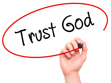 trust in god: Man Hand writing Trust God  with black marker on visual screen. Isolated on white. Business, technology, internet concept. Stock Photo