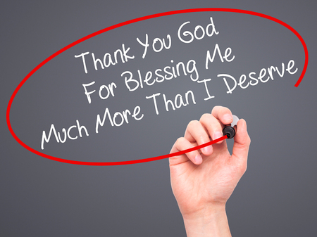 deserve: Man Hand writing Thank You God For Blessing Me Much More Than I Deserve with black marker on visual screen. Isolated on grey. Business, technology, internet concept. Stock Photo