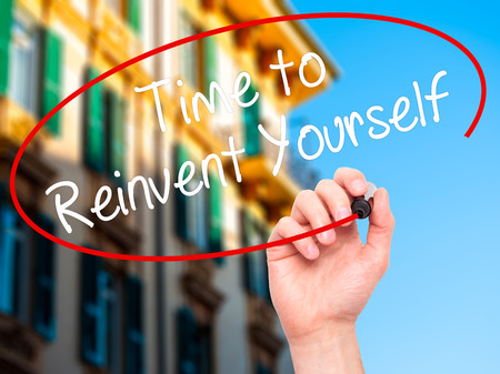 revitalize: Man Hand writing Time to Reinvent Yourself with black marker on visual screen. Isolated on city. Business, technology, internet concept. Stock Photo