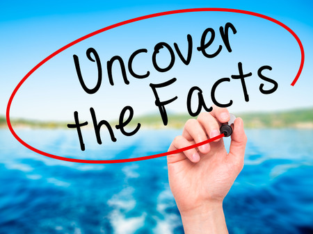 uncover: Man Hand writing Uncover the Facts with black marker on visual screen. Isolated on nature. Business, technology, internet concept. Stock Image