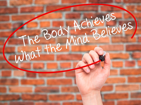 believes: Man Hand writing The Body Achieves What the Mind Believes with black marker on visual screen. Isolated on bricks. Business, technology, internet concept. Stock Photo
