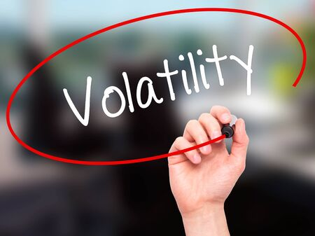 volatility: Man Hand writing Volatility with black marker on visual screen. Isolated on office. Business, technology, internet concept. Stock Photo
