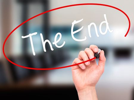conclusive: Man Hand writing The End with black marker on visual screen. Isolated on office. Business, technology, internet concept. Stock Photo