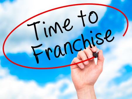 Man Hand writing Time to Franchise with black marker on visual screen. Isolated on sky. Business, technology, internet concept. Stock Photo