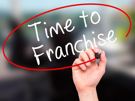 Man Hand writing Time to Franchise with black marker on visual screen. Isolated on office. Business, technology, internet concept. Stock Photo Stock Photo