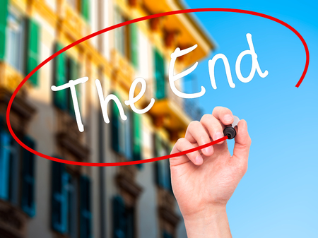 conclusive: Man Hand writing The End with black marker on visual screen. Isolated on city. Business, technology, internet concept. Stock Photo