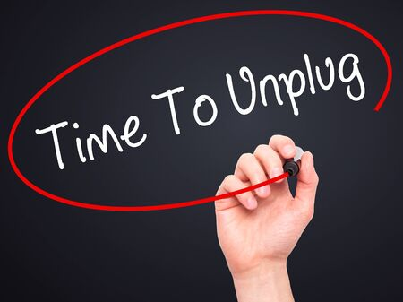unplugging: Man Hand writing Time To Unplug with black marker on visual screen. Isolated on black. Business, technology, internet concept. Stock Photo