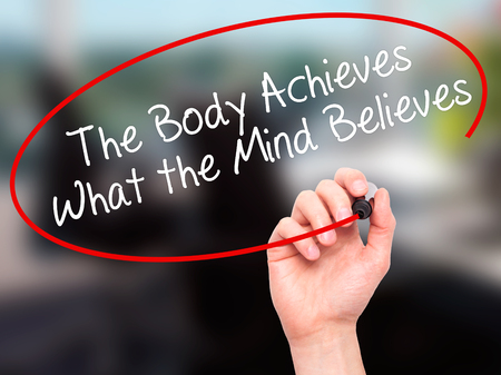believes: Man Hand writing The Body Achieves What the Mind Believes with black marker on visual screen. Isolated on office. Business, technology, internet concept. Stock Photo Stock Photo