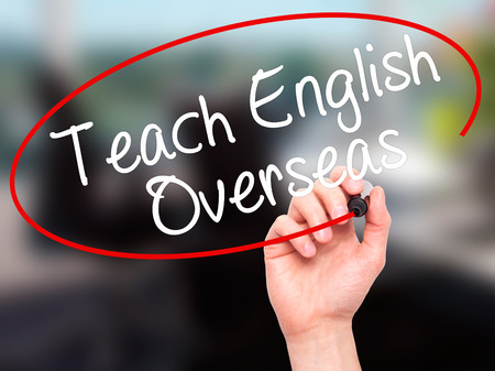 recruiters: Man Hand writing Teach English Overseas with black marker on visual screen. Isolated on office. Business, technology, internet concept. Stock Photo