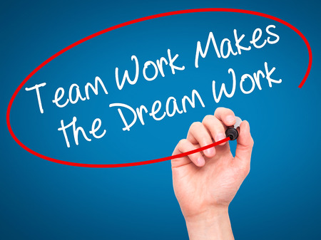 teamwork business: Man Hand writing Team Work Makes the Dream Work with black marker on visual screen. Isolated on blue. Business, technology, internet concept. Stock Image