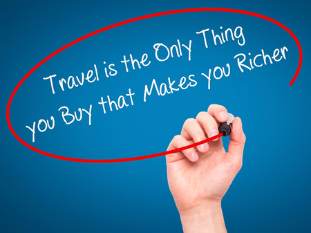 richer: Man Hand writing Travel is the Only Thing you Buy that Makes you Richer with black marker on visual screen. Isolated on blue. Business, technology, internet concept. Stock Photo