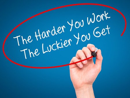 harder: Man Hand writing The Harder You Work The Luckier You Get  with black marker on visual screen. Isolated on blue. Business, technology, internet concept.