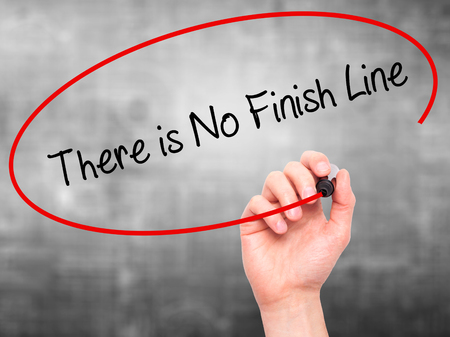 not ready: Man Hand writing There is No Finish Line with black marker on visual screen. Isolated on grey. Business, technology, internet concept. Stock Photo