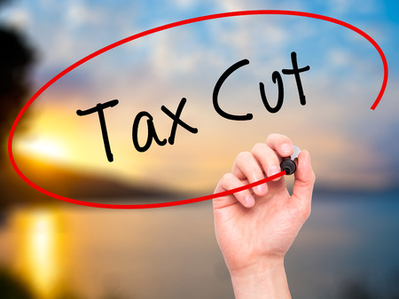 pay cuts: Man Hand writing Tax Cut with black marker on visual screen. Isolated on nature. Business, technology, internet concept. Stock Photo
