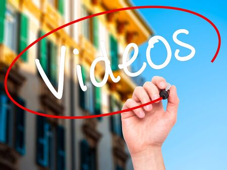 televisor: Man Hand writing Videos with black marker on visual screen. Isolated on city. Business, technology, internet concept. Stock Image Stock Photo
