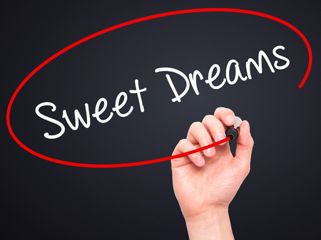 endearment: Man Hand writing Sweet Dreams with black marker on visual screen. Isolated on black. Business, technology, internet concept.