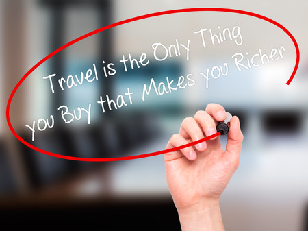 richer: Man Hand writing Travel is the Only Thing you Buy that Makes you Richer with black marker on visual screen. Isolated on office. Business, technology, internet concept. Stock Photo
