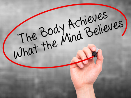 believes: Man Hand writing The Body Achieves What the Mind Believes with black marker on visual screen. Isolated on grey. Business, technology, internet concept. Stock Photo