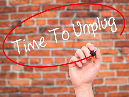 unplugging: Man Hand writing Time To Unplug with black marker on visual screen. Isolated on bricks. Business, technology, internet concept. Stock Photo