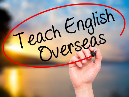 Man Hand writing Teach English Overseas with black marker on visual screen. Isolated on nature. Business, technology, internet concept. Stock Photo