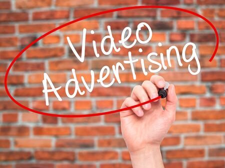 infomercial: Man Hand writing Video Advertising with black marker on visual screen. Isolated on bricks. Business, technology, internet concept. Stock Photo Stock Photo