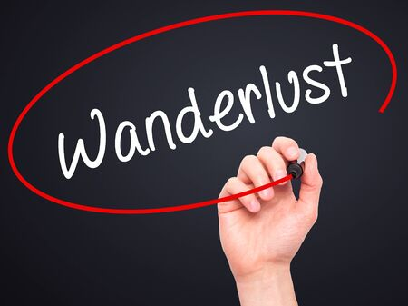 wanderlust: Man Hand writing Wanderlust with black marker on visual screen. Isolated on black. Business, technology, internet concept. Stock Photo