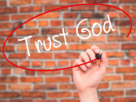 trust in god: Man Hand writing Trust God  with black marker on visual screen. Isolated on bricks. Business, technology, internet concept. Stock Photo