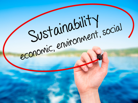 economic theory: Man Hand writing Sustainability  economic, environment, social with black marker on visual screen. Isolated on nature. Business, technology, internet concept.