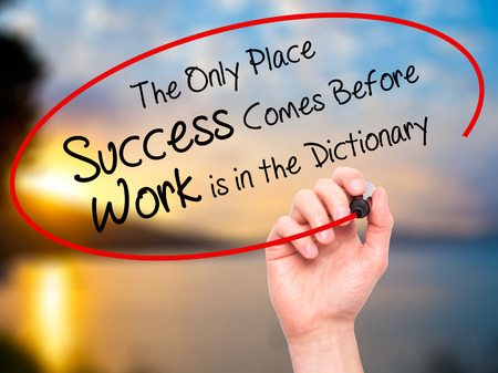 dictionary: Man Hand writing The Only Place Success Comes Before Work is in the Dictionary with black marker on visual screen. Isolated on nature. Business, technology, internet concept. Stock Photo