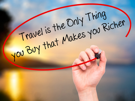 richer: Man Hand writing Travel is the Only Thing you Buy that Makes you Richer with black marker on visual screen. Isolated on nature.