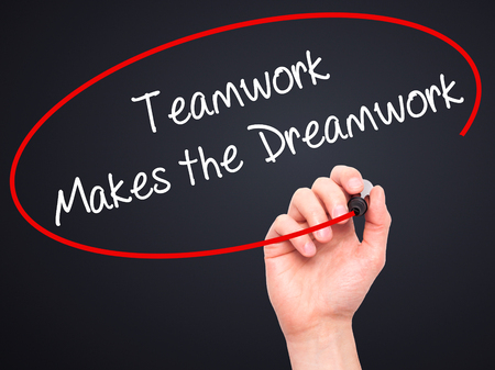 makes: Man Hand writing Teamwork Makes the Dreamwork with black marker on visual screen. Stock Photo