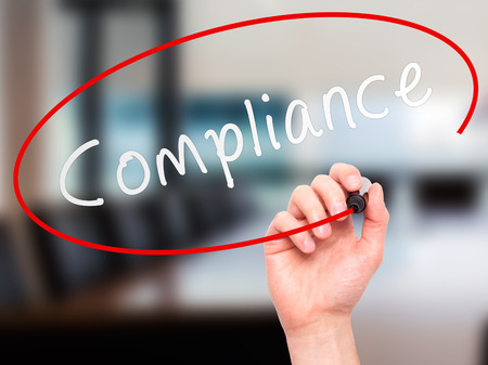 conformation: Man Hand writing Compliance with marker on transparent wipe board. Isolated on office. Business, internet, technology concept. Stock Photo Stock Photo